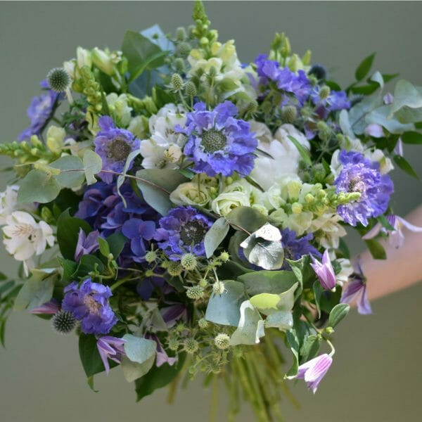 photo showing a sample of a lilac blue and white seasonal bouquet available from Kensington flowers London