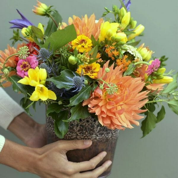Photo showing a sample bucket of flowers, in orange and yellow colours available for Kensington flowers, London