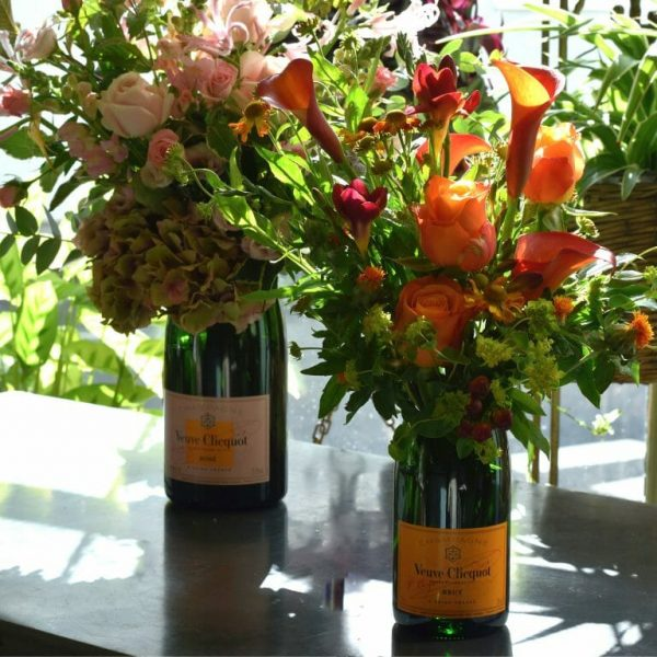 Photo showing a sample image of champagne flower bottle vase arrangements available from Kensington Flowers London