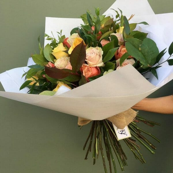 Photo showing a sample of a wrapped Classic rose bouquet mixed colours available to order from Kensington flowers London