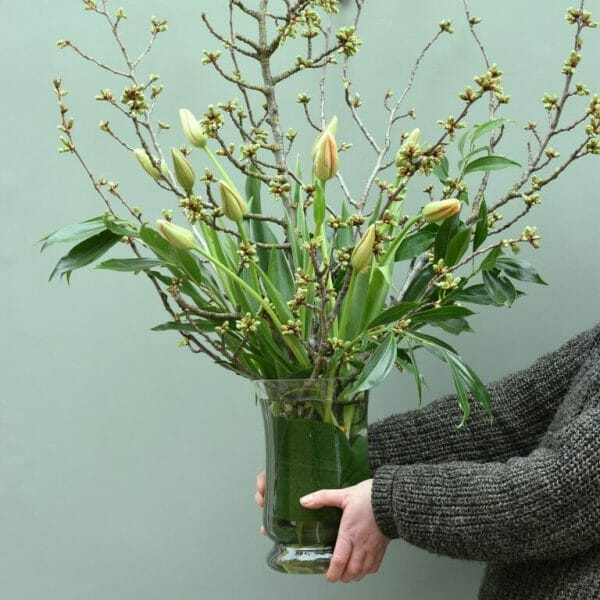 Photo showing a sample of a Florist choice vase arrangement, of French tulips and blossom branches available from Kensington flowers London