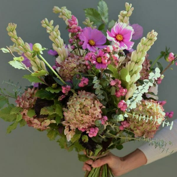Photo showing a sample of a seasonal hand tied bouquet in dusky pink autumn colours available as sample of a gift set of Flowers and lemon drizzle cake available to order at Kensington flowers London