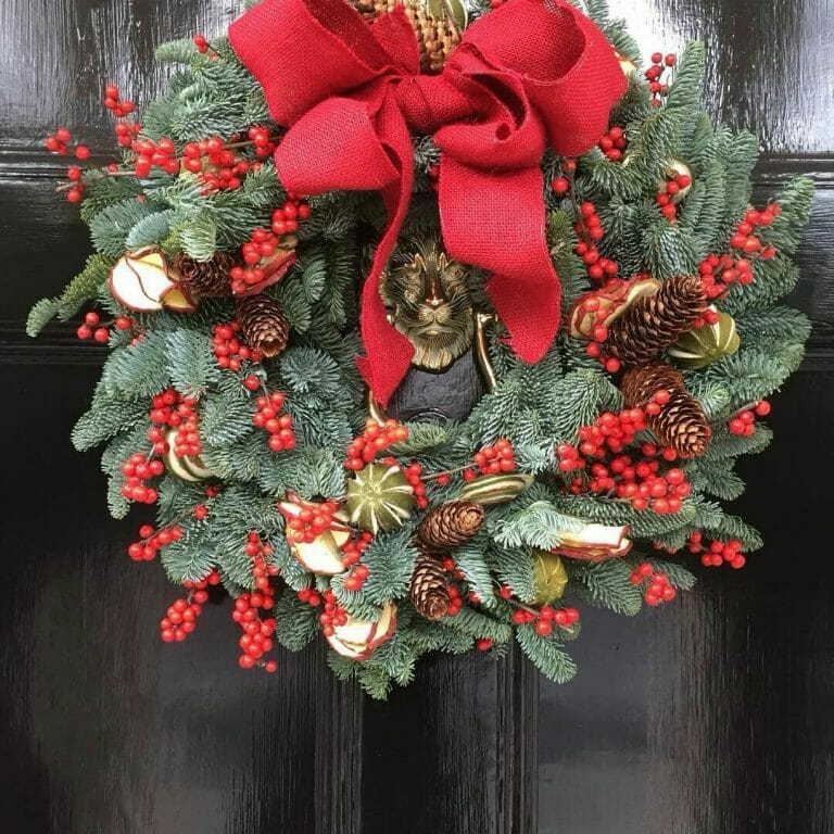 Photo showing a sample of a Pine, fruits, ilex berry and cone door wreath Kensington flowers London