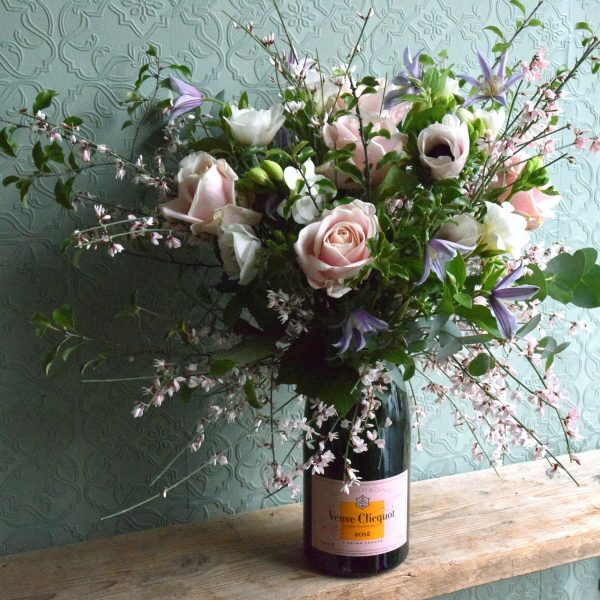 Photo showing a sample of a Champagne flower bottle vase filled with seasonal flowers, available to order from K