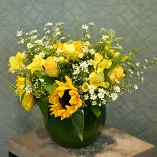 Photo showing a sample of a Scented garden vase arrangement of sunflowers, freesia vase arrangement Kensington flowers