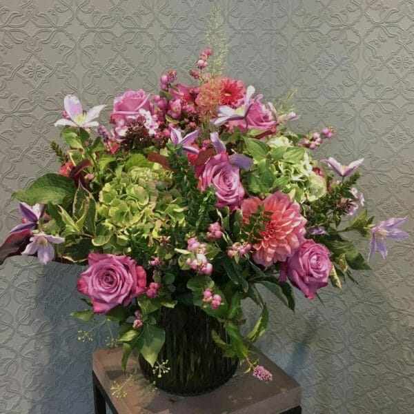 Photo showing a sample of a Seasonal classic vase in pink and lavender colours available to order from Kensington flowers London