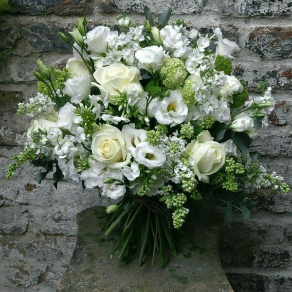 Photo showing a sample of a white Seasonal Hand Tied Bouquet available to order from Kensington Flowers London