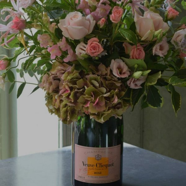 Photo showing a sample of an up-cycled Rose Champagne flower bottle vase, filled with flowers, available to order from Kensington flowers London