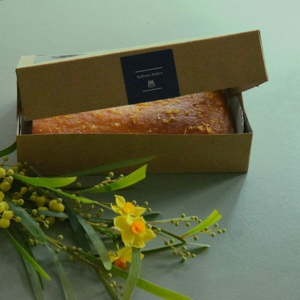Photo showing a sample of a Balham bakes Lemon drizzle cake presented in a silver tin, available to order with flowers from Kensington flowers London as part of a gift set