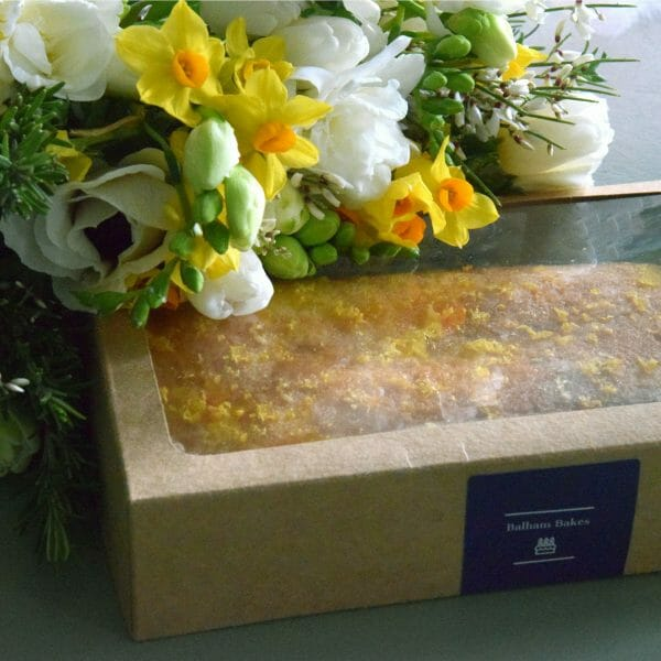 Photo showing a sample of a gift set of Flowers and lemon drizzle cake available to order at Kensington flowers London