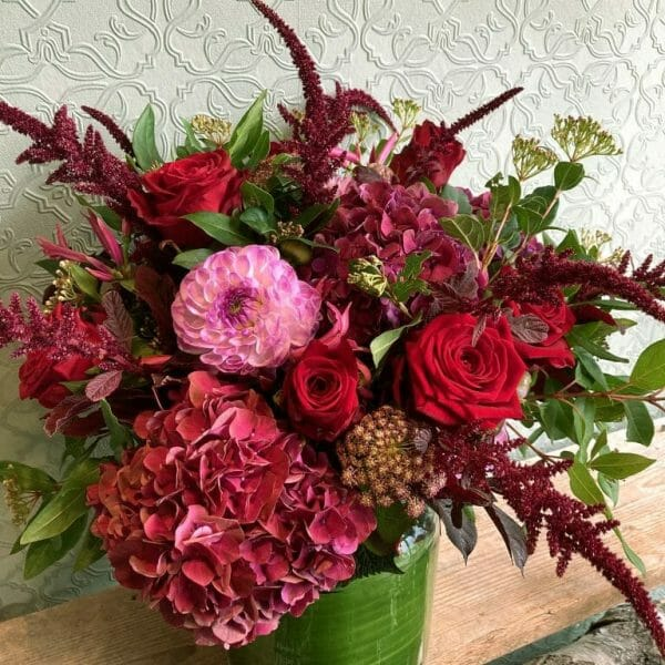 Photo showing a sample of a red rose and pink seasonal vase arrangement available to order from Kensington flowers London
