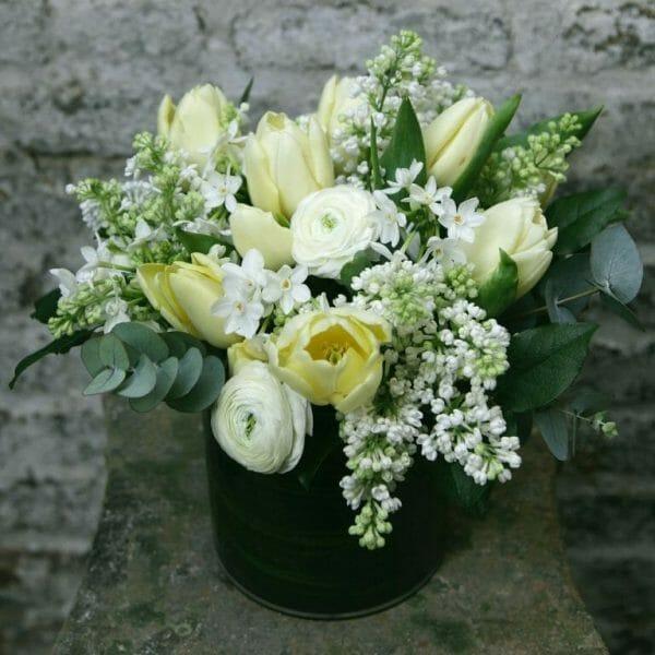 Photo showing a sample of a Seasonal Classic Vase Arrangement - spring lemon and white colours - Kensington flowers, London