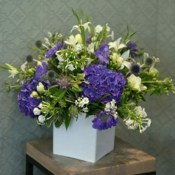 Photo showing a sample of a Studio florist choice Vase Arrangement - purple and white colours - available from Kensington flowers, London