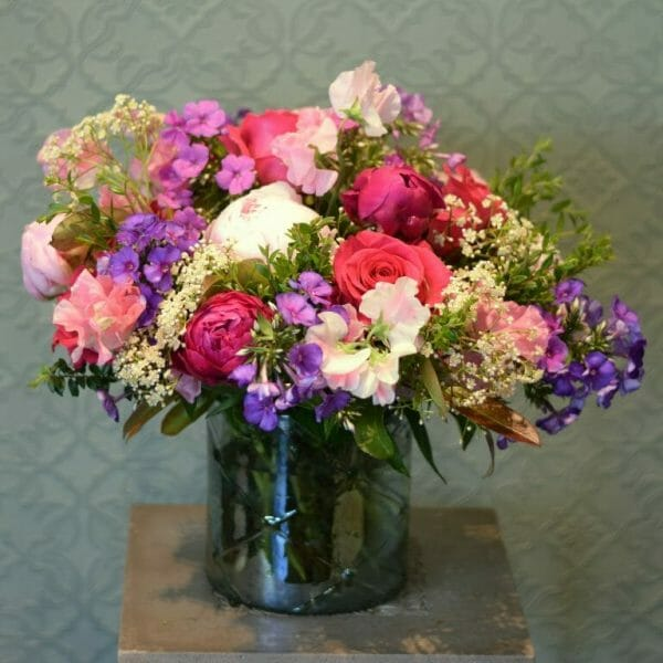 Photo showing a summer vase arrangement of peonies, Roses, and sweet peas in mixed colours available to order from Kensington Flowers London